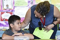 A Fresno Unified teacher speaking to a young student.